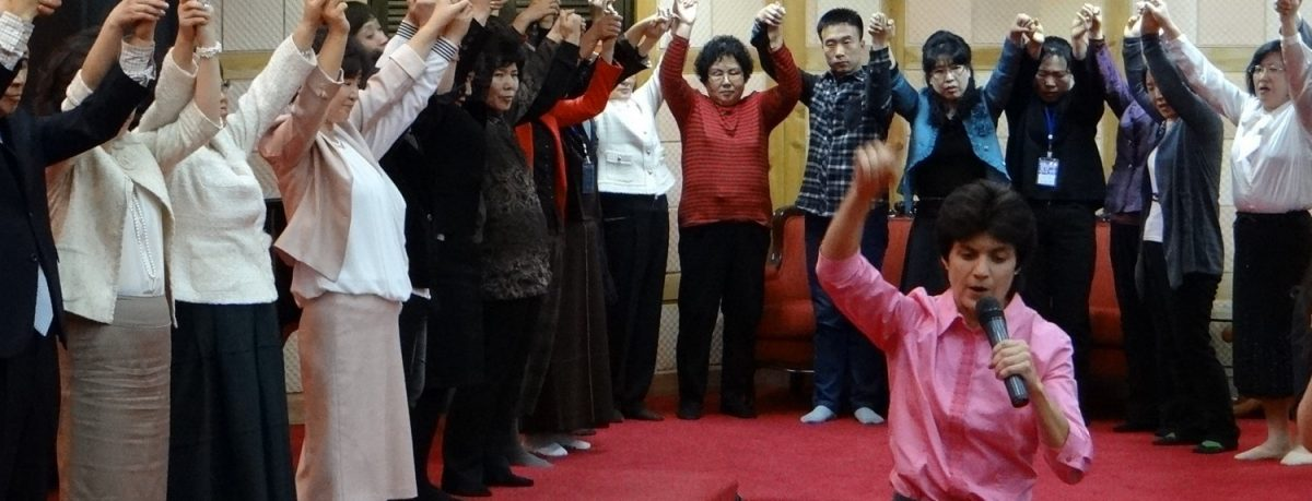 cropped-Leanna-preaching-Korea-circle-hands-up